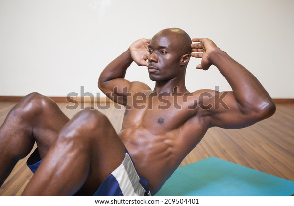 Side view of muscular man doing abdominal crunches in gym