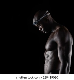 Side view of muscular young man wearing swimming goggles with wet body looking down over black background with copy space. Strong african male swimmer after training session.