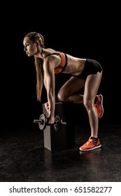 Side view of muscular young sportswoman standing on knee and exercising with dumbbell