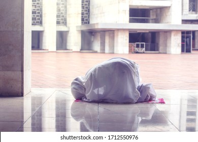 Side view of muslim woman doing prostration gesture while doing worship to Allah in the mosque