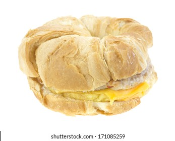 A side view of a nicely browned prepared breakfast croissant filled with a sausage patty, egg, cheese on white.