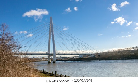Side view of the Northern Spire Bridge in Sunderland taken from the River Wear's embankment on a sunny spring morning.  Showing blue sky and minimal white clouds.