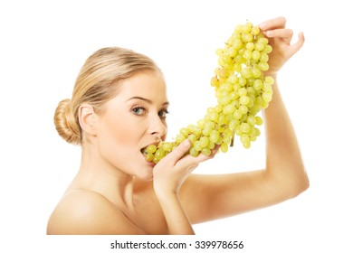 Side view of nude woman eating green grapes, looking at the camera