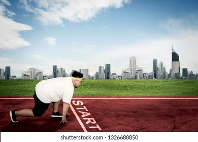Side view of an obese man ready to run while kneeling on the start line. Shot at outdoors