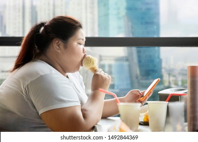 Side view of obese woman enjoying leisure time with a mobile phone and ice cream cone in the cafe