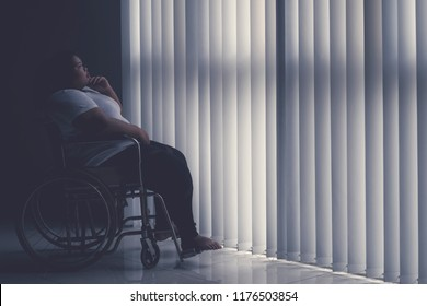Side view of obese woman looks pensive while sitting in the wheelchair by the window. Shot in the hospital