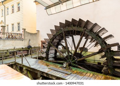 Side view of an old ancient wet wooden waterwheel with surrounding city buildings and architecture in Prague.