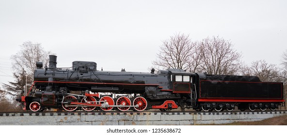 Side view of old classic black steam locomotive with red decoration on railroad track