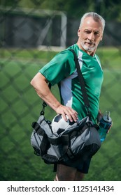 side view of old man with sportive water bottle and bag on soccer field