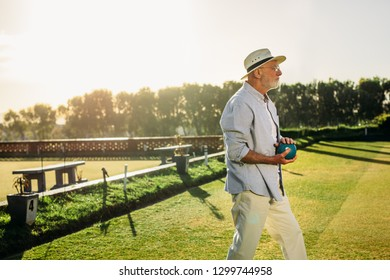 Side view of an old man standing in a park playing boules on a sunny day. Senior man in hat playing boules in a lawn with sun flare in the background.