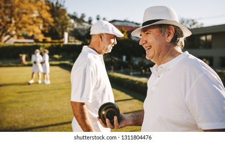Side view of an old man standing in a park playing boules on a sunny day. Senior man in hat playing boules in a lawn with friends.