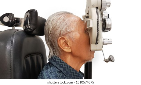 Side view of old man visiting optometrist in the hospital while examining his eyes by using a phoropter