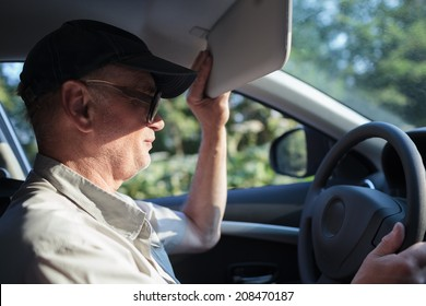 Side view of an old man at the wheel trying to hide himself from the sun with a sun visor