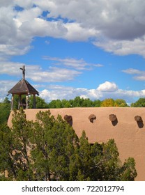 Side view of old mission adobe church surrounded by trees.