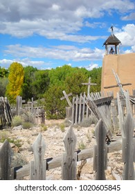 Side view of old Mission church with graveyard and faded wooden crosses and picket fence in foreground set in Southwest landscape.