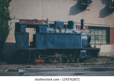 Side view of an old vintage steam locomotive waiting in front of a shed in Macomer, Sardinia, hoping to recieve a bright new future as a museum locomotive