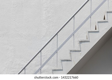 side view of old white outside fire escape emergency staircase with metal handrail railing and concrete wall.
