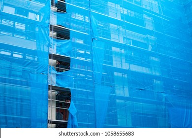 Side view on an apartment building under construction, with exterior scaffolding covered in a blue tarp, with space for text on right