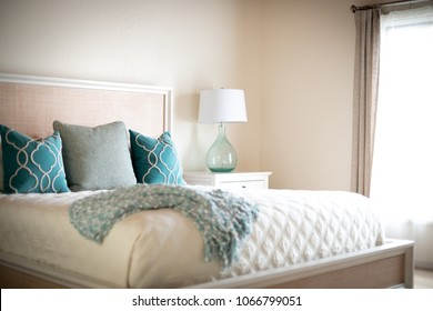 Side view on blue and green decorative throw pillows on a king size bed, with white quilt and linens, and space for text