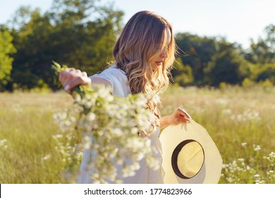 Side view on caucasian girl wearing white dress walking in the field - Beautiful young woman in nature summer day with flowers in hand and hat - Half length new life solitude grief rejection concept