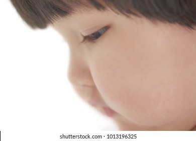 Side view on the child on studio background. Close-up photo