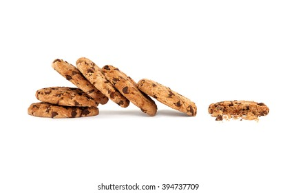 Side view on collapsed stack of six yummy chocolate chip cookies next to a partially eaten one with crumbs, isolated on white background with copy space