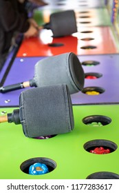 Side view on a colorful Whack a Mole game at a carnival and arcade, with padded mallets and space for text on top and bottom