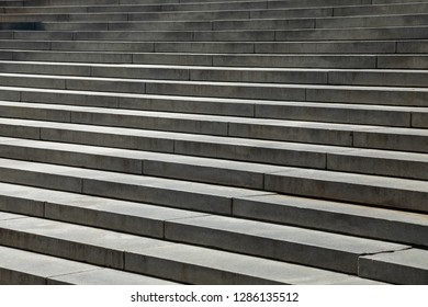 Side view on concrete steps in front of a neoclassical building, in an architectural background