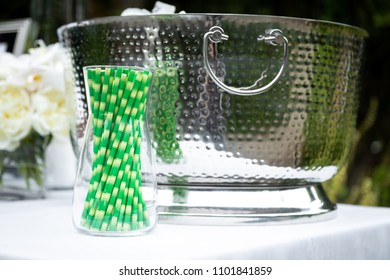 Side view on a container of green paper straws, a no plastic ecofriendly alternative,  in front of a chrome punch bowl, with space for text on the right