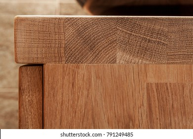 Side view on corner of wooden bathroom table with door made of three flat wooden boards with wood texture and edges lit with artificial light
