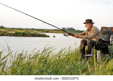 Side view on elderly gray-haired man fishing on lake in nature, patience and recreation concept.Portrait of senior caucasian fisherman with rod sitting on chair in nature, countryside