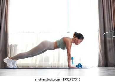 side view on fit woman doing push ups at hone, training doing exercises, beautiful caucasian female workout alone, concentrated on exercise, athletic woman in good shape