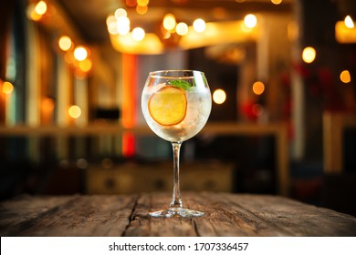 Side view on fresh cool cocktail gin tonic with a slice of orange and ice in a wine glass on the woden table, horizontal format