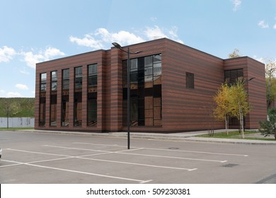 Side view on the generic red brick office building with parking lot
