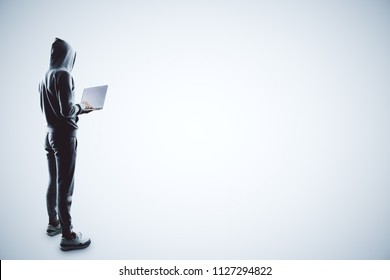 side view on hacker in grey sport suit with laptop at white background.