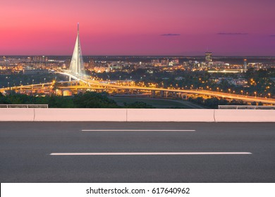 Side view on highway and the city in background, shiny new bridge, as well as modern access roads at idyllic purple sunset.
