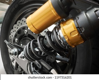 Side view on motorcycle rear chassis suspension with damper, coil spring,  wheel rim with tire, disc brake. Moto bike suspension close up