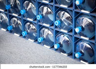 Side view on a rack with full and empty jugs of filtered water refills
