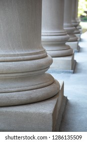 Side view on a row of round neoclassical columns at a federal courthouse, in an architectural background, with space for text on the right