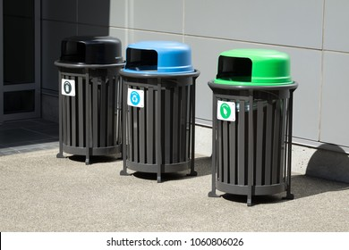Side View On A Row Of Trash Receptacles, With A Compost And Recycling Bin  Beside