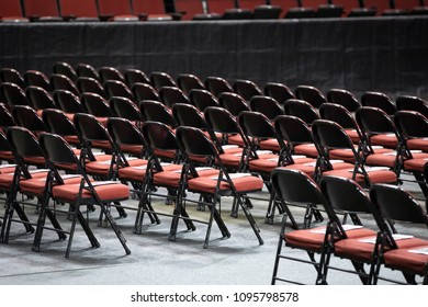 Side view on rows of black folding chairs with red cushions, at a gradution ceremony or concert, with space for text on top