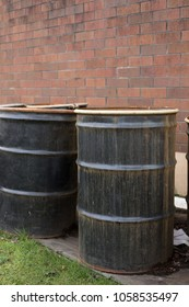 Side view on the a rusted 55 gallon drum, beside barrels of oil, at a chemical disposal facility