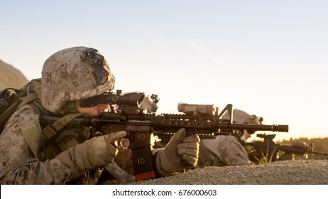 Side view on Soldiers Lie Down on the Hill, Aiming through the Assault Rifle Scope in Desert Environment in Sunset Light.