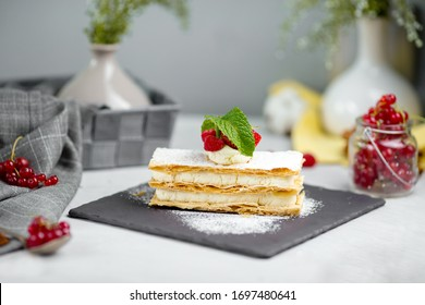 Side view on strawberry and whipped cream mille-feuille with fresh berries on a black stone board on the white background, horizontal