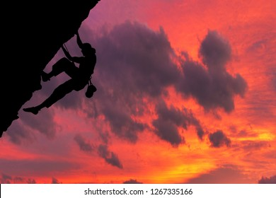 Side view on the young mountainer. Silhouette mountainer in action. The mountainer climbs to a hard route on the rock to reach its goal and success. Red sky and clouds in the background.