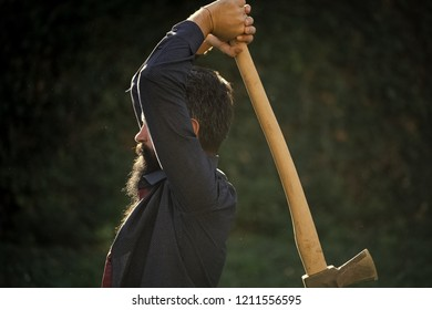 Side view of one strong stylish male logger of young man with long lush black beard and moustache in shirt holding wooden axe standing near wall with climber plant outdoor, horizontal picture