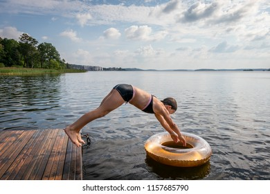 Side view of one young girl diving into water and swim ring from a jetty at a summer lake.