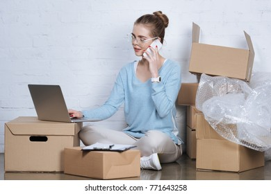 side view of online shop owner talking on smartphone while working on laptop at home office
