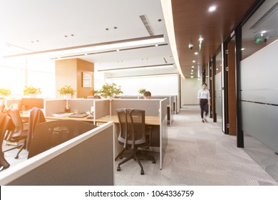Side view of open space office interior with rows of computer tables with desktops standing on them