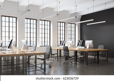 Side view of an open space office with a black wall, many tables with computers on them and a concrete floor. 3d rendering.